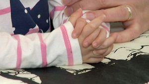 Pieni tyttö pitää käsiä ristissä pöydällä.