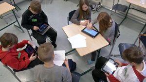 Koululaisia tekemässä töitä tablet-tietokoneilla.