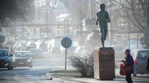 Liikenne nostattaa pölyä Turun keskustassa Paavo Nurmen patsaan ympärillä.