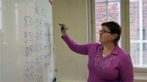 Nainen kirjoittaa taululle tussilla