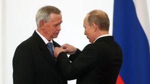 Vladimir Putin asettaa jotain iäkkään miehen, Valentin Rasputi rintaan.
