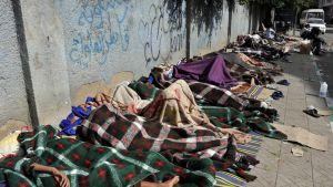 Eritreasta paenneet nukkuvat jalkakäytävällä odottaessaan apua YK:n pakolaisavulta Sanaassa, Jemenissä, toukokuussa 2014.