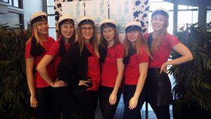 Kuusi nuorta naista, joilla teekkarilakit päässä.