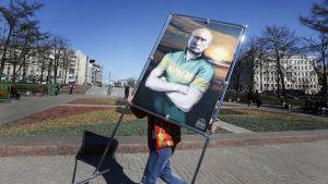Mies kantaa Putinia esittävää julistetta.