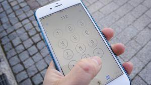 Ihminen näppäilee hätänumeroa puhelimeensa.