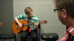 Kuvassa poika soittaa kitaraa.