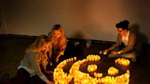 Ihmiset sytyttävät kynttilöitä Earth Hourin kunniaksi