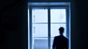 Ihminen seisoo ikkunan ääressä