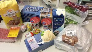 Pöydällä jauhelihaa, jauhoja, maitoa, suklaamunia, paahtoleipää, jugurttia, grillibroileria, salaattia ja jäätelöä