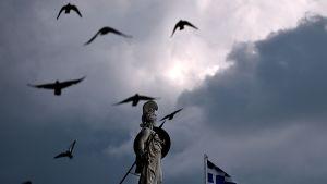 Kreikkalaisen jumalattaren veistos on Kreikan lipun vieressä pimenevässä Ateenassa. Lintuparvi lentää veistoksen viereltä.