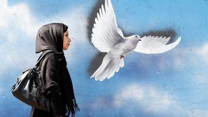 Mustiin vaatteisiin pukeutunut nainen kävelee rauhankyyhkymaalauksen ohi.