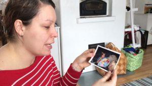 Minna Haataja muistelee kotisynnytyskokemustaan valokuvia katselemalla.