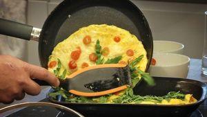 Mies valmistaa munakasta keittiössä.