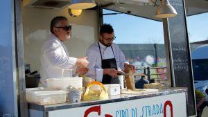 Kaksi miespuolista kokkia pienessä vaunussaan.