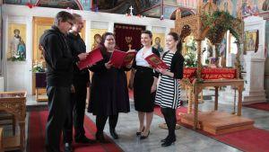 Viisi laulajaa koristellussa kirkossa.