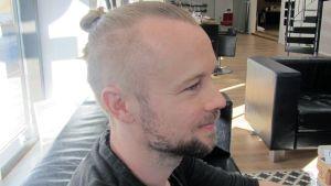 Kuvassa nutturapäinen mies parturitiloissa