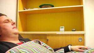Mies nukkuu peiton alla.
