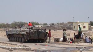 Hyökkäysvaunu ja siviilipukeisia miehiä sen ympärillä.