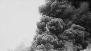 Mustavalkoinen kuva jossa suuri joukko sotilaita katsoo palavaa rakennusta.