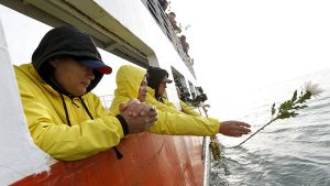Keltaisiin sadetakkeihin sonnustautuneet omaiset ovat nojautuneet lautan kannen reunaa vasten. Yksi heistä, keskellä oleva nainen, on juuri heittämässä muistokukkaa mereen.