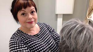 Kampaajamestari Sara Soini esittelee peruukkia.