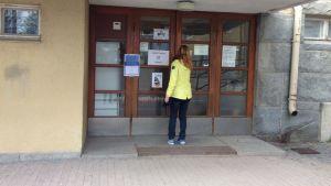 Nuori nainen avaamassa Pispalan koulun ovea.