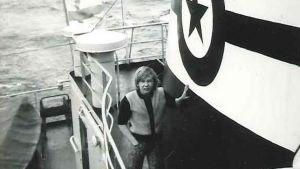 Kuvassa nuori mies laivalla taustalla näkyy merta.