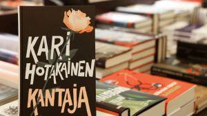 Kari Hotakaisen Kantaja-kirja muiden teosten seassa.