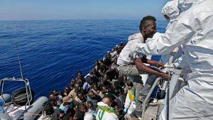 Valokuvassa Italian viranomaiset auttavat veneessä olevia siirtolaisia laivaansa 22. huhtikuuta. Veneessä oli arviolta 200 matkustajaa.