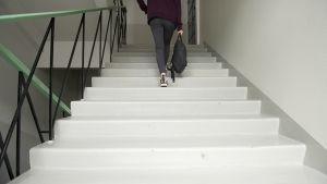 Nuori nainen kävelee ylös portaita.