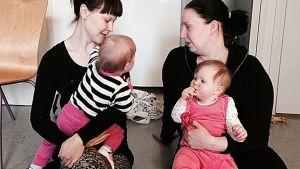 Kaksi äitiä keskustelee lapset sylissään