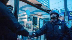 Mielenosoittaja ja poliisi kättelevät 25. huhtikuuta.