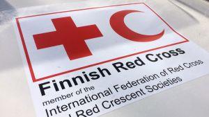Suomen Punaisen Ristin merkki auton konepellillä.