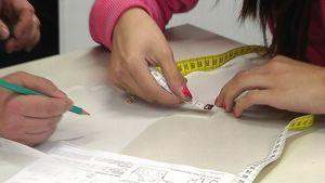 Koululaistytön kädet pitelevät mittanauhaa, opettajan käsi lyijykynää.