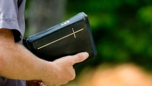 Raamattu miehen kädessä.