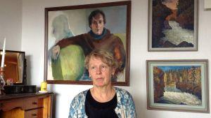 Eve Jaakkola kotonaan, taustalla Hanna Saarikosken maalaus Jyri Jaakkolasta