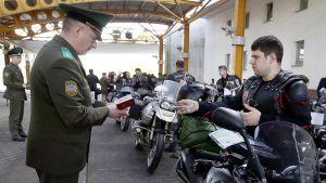 Valkovenäläinen rajavartija tarkastamassa Yön Susien jäsenten passeja raja-asemalla.