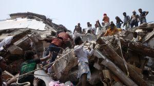 Vapaaehtoiset auttavat eloonjääneiden etsimisessä romahtaneen Rana Plazan raunioista huhtikuussa 2013.