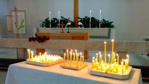 Kynttilöitä palaa kirkon alttarin edustalla.