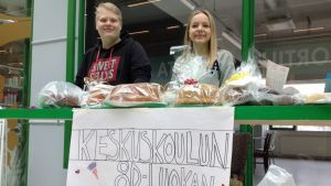 Lucas Holm ja Eevi Peltokangas seisovat myyjäispöydän takana.