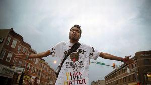 """Nuori mustaihoinen mies on levittänyt kätensä ja seisoo keskellä katua. Hänellä on valkoinen t-paita, jossa on karhun pään kuva. T-paidassa lukee muun muassa """"Black lives matter""""."""