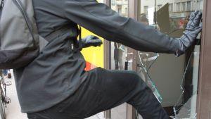 Kuvassa mies särkee Helsingin Sörnäisissä sijaitsevan ruokakaupan oven lasin.