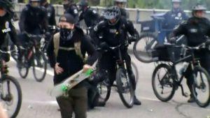 Mielenosoittaja ja poliiseja Seattlessa.