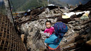 Nainen kantoi lastaan maanjäristyksen episentrumissa olleen Barpakin kylän jäänteissä Nepalissa.