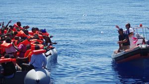 MOAS:n (Migrant Offshore Aid Station) heittävät juomavesipulloja pakolaisten kumiveneeseen Maltan vesillä elokuussa 2014.