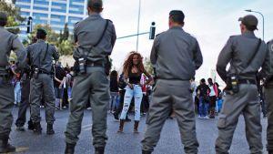 Mielenosoittaja keskustelee poliisien kanssa.