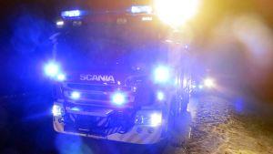Paloauto pimeällä tiellä