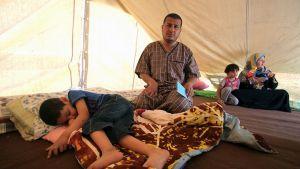 Pakolaisperhe teltassa.