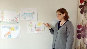 Koulupsykologi Marika Ylhäinen osoittaa lasten piirtämää kuvaa vuodenajoista.