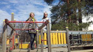 Kaksi opettajaa seisoo lasten kiipeilytelineen päällä.